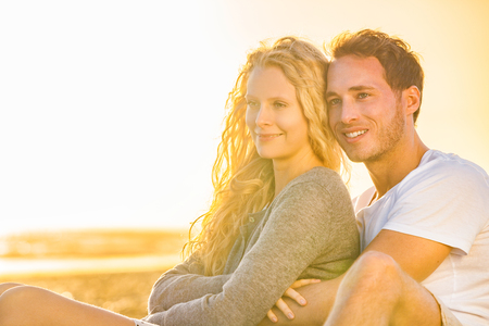 Young happy couple hugging on beach watching sunset relaxing on summer holidays. People on vacation lifestyle, man holding blonde woman girlfriend.