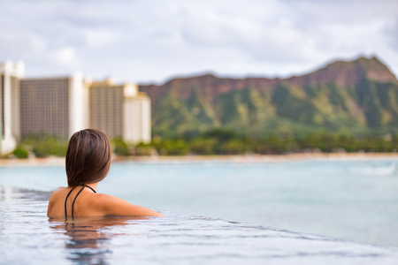 Hawaii vacation Honolulu travel tourist woman relaxing in swimming infinity pool at luxury resort hotel in Waikiki beach, watching sunset. Girl on USA summer travel landscape banner panoramic. Stock Photo