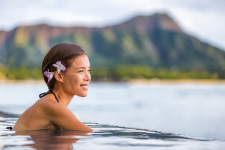 Asian woman relaxing in infinity pool at luxury spa resort in Hawaii, watching ocean beach from hotel. Girl tourist on travel vacation in Waikiki, Honolulu, USA holiday. Summer outdoor wellness. Imagens