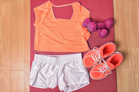 Gym fitness clothing on floor for strength training workout at home top view. Orange matching t-shirt and running shoes, white shorts, pink girly dumbbells weights on mat. Banque d'images