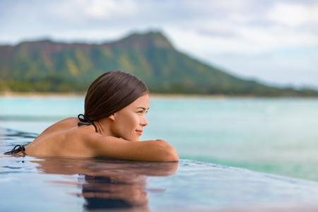 Luxury vacation travel woman relaxing in infinity swimming pool on summer beach resort. Asian girl tourist on wellness spa relaxation watching sunset outside in nature landscape background.