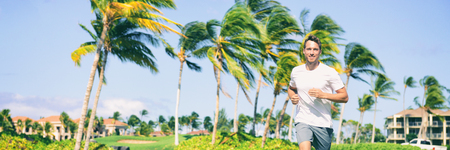 Runner running man jogging in tropical summer outdoors happy living a healthy and active lifestyle . Panoramic background with palm trees, Jogger athlete training outside.