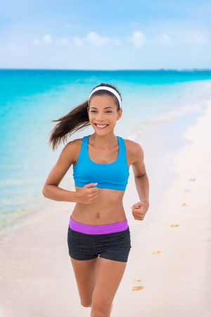 Fitness girl running on beach in fashion activewear clothes. happy Asian woman jogging with blue sports bra and shorts on morning training outside. Summer travel.
