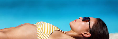 Beach vacation woman sun tanning bikini wearing sunglasses for solar protection eye care. Young girl lying down sunbathing relaxing. Skincare UV sun shade banner panorama. Banque d'images