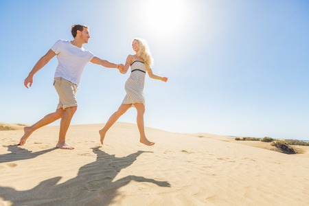 Sun beach summer vacation couple running of joy holding hands. Blonde woman happy carefree with young man, relaxing on honeymoon holiday.
