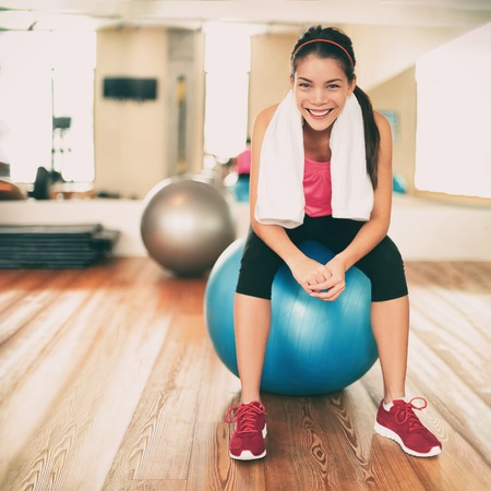 Fitness girl exercising happy in gym resting on pilates exercise ball after training class. Asian woman sweating with towel on weight loss workout portrait. Active healthy lifestyle.