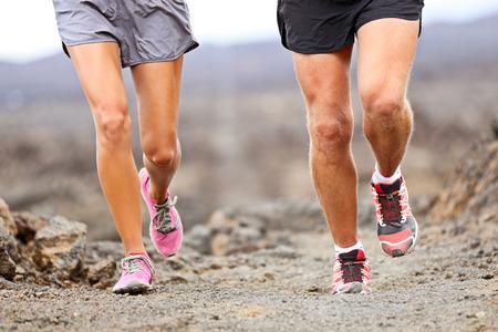 Runners running shoes on trail run. Ultra running athletes legs closeup on desert trail.
