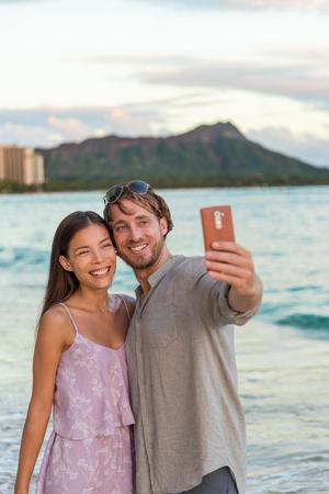 Couple taking phone selfie on Waikiki beach at sunset, Honolulu, Hawaii travel vacation. Young people on hawaiian holidays. Romantic holiday destination for honeymoon. Stock Photo