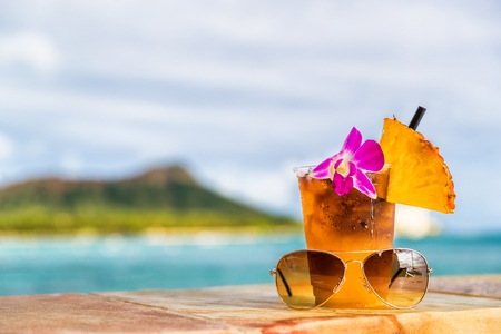 花、パイナップル、サングラスを備えたワイキキビーチバーで、ハワイマイタイカクテルドリンクを楽しめます。ハワイ州ホノルルの海とダイヤモ 写真素材