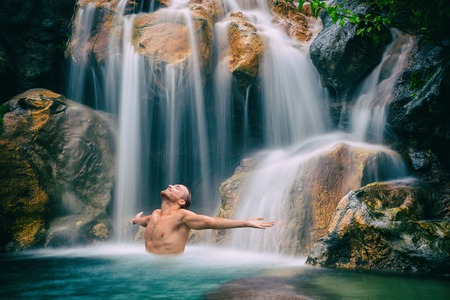 Man relaxing with freedom open arms in waterfall in tropical nature. Wellness spa concept in holiday nature. Stock Photo