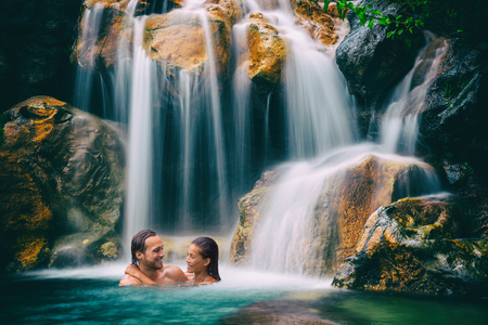 Waterfall couple relaxing in natural pool in tropical nature forest. Romantic getaway in hawaiian destination people swimming in travel vacation.