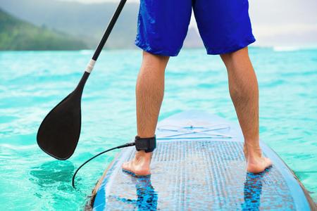 Hombre del tablero de paleta que hace paddleboard de pie en el océano. Atleta paddleboarding en tabla de surf SUP en Hawaii beach travel. Primer plano de las piernas de pie a bordo. Foto de archivo
