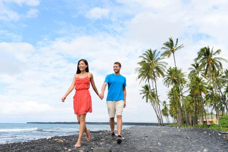 Vacation couple walking holding hands on beach travel destination. Happy summer holidays. Asian woman caucasian man multiracial people together having fun. Big island, Hawaii.
