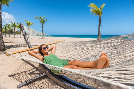 Happy girl relaxing on beach hammock in tropical vacation resort hotel. Holidays in the Caribbean tanning under the sun. Woman wearing sunglasses and green dress relax lying down on sun lounger bed.