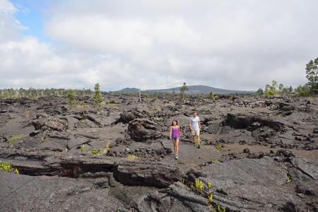 Hawaii destination travelers couple hiking in volcanic rocks on Kilauea volcano in Big island of Hawaii