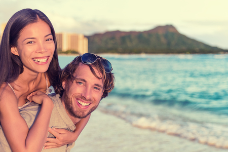 Happy interracial couple, woman piggybacking on man on Waikiki beach with Diamond Head Mountain landscape. Healthy people portrait, Honolulu, Hawaii. Travel holidays destination. Banque d'images