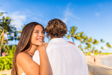 Couple hugging on tropical beach Asian woman holding man looking away pensive. Beautiful girlfriend happy smiling at sunset with boyfriend.