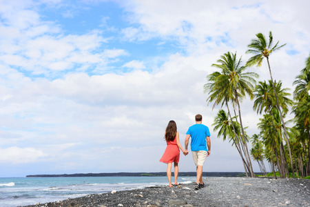 Couple walking on Hawaii secluded black sand volcanic beach on the Big island of Hawaii, hawaiian destination tropical travel for summer vacations. People from behind relaxing on walk. Фото со стока - 95795490