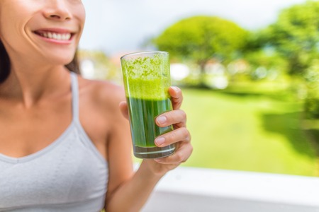 Green smoothie healthy lifestyle fitness woman drinking spinach juice cleanse in summer background at home. Happy fit girl living active life juicing.