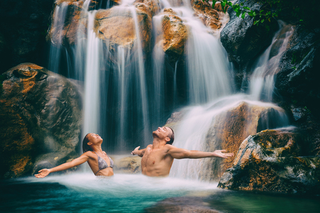 Wellness spa waterfall couple relaxing in nature waterfall with open arms in freedom. Relaxation in waterfall in tropical vacation. Holidays destination in paradise. Фото со стока - 95795605