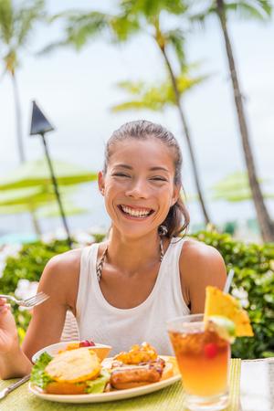 Happy woman at restaurant eating Hawaii burger with pineapple and karaage fried chicken. Hawaiian japanese fusion food. Asian girl at hotel restaurant table during summer travel vacation.