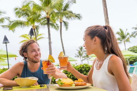 Couple eating at hotel restaurant on Hawaii travel vacation beach drinking hawaiian drink mai tai. Happy people toasting cheers with cocktails. Summer holidays at resort. Stock Photo