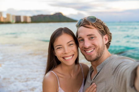 Selfie couple on Waikiki beach taking pictures with smartphone during night out walk on beach summer vacations in Honolulu, Hawaii. Travel destination. Young people having fun on hawaiian holidays. Stock Photo