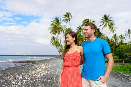 Hawaii couple enjoying beach holidays looking at view of ocean from black sand volcanic beach on Big Island of Hawaii, hawaiian travel vacation.