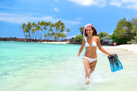 Summer beach vacation fun snorkel girl splashing water . Happy bikini woman relaxing in tropical ocean with fins and snorkeling gear. Exotic travel destination paradise in Big Island, Hawaii, USA. Banco de Imagens