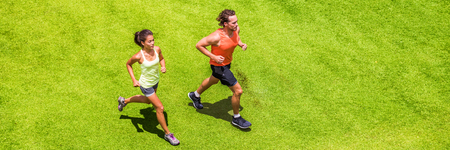 Runners running people couple fitness banner. Healthy active lifestyle. Active couple jogging together on grass park view from above. Summer weight loss training program. Banque d'images