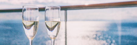 Two champagne glasses or sparkling white wine flutes on ocean landscape background, panorama banner for luxury travel vacation. Drinks in sun on couple cruise holiday.