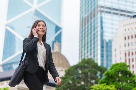 Asian businesswoman talking on mobile phone walking in Hong Kong city street to office, skyscrapers cityscape background. Young woman on smartphone happy. Multiracial Chinese Caucasian lady.