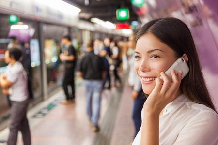 Zakenvrouw op metro metro pendelen openbaar vervoer station praten aan de telefoon tijdens het lopen naar aankomende trein. Aziatische vrouw gelukkig met behulp van mobiele mobiel app voor gesprek.