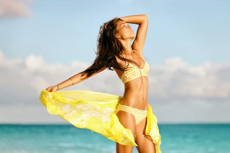 Modelo asiático atractivo del cuerpo del bikini libre en la playa que se relaja con las piernas delgadas y el estómago entonado en traje de baño amarillo y bufanda - tratamiento del laser de las celulitis, pérdida de peso, concepto de la salud.