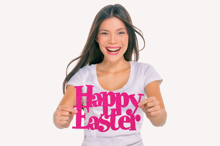 Happy Easter party sign young girl showing text signage. Asian woman holding cutout of title on studio background. For Easter holiday spring season celebration. Stock Photo