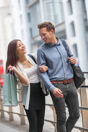 Couple walking in city street together happy. Asian woman and man shopping in Hong Kong, China holding shopping bags. Multiracial Chinese woman girl and Caucasian man smiling urban living.