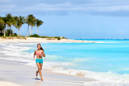 Fitness runner woman running on tropical white sand beach nature landscape outdoors. Beautiful nature in Caribbeans with person jogging living a healthy lifestyle for weight loss in summer. Stock Photo