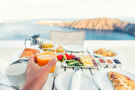 Luxury travel resort breakfast in room service at fancy hotel restaurant with amazing balcony view over Santorini island, Oia, Greece. Europe vacation food selfie. Man drinking morning orange juice.