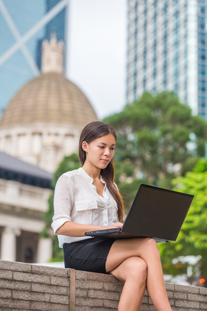 Business woman with computer laptop working outside looking at screen in business district, Central, Hong Kong. Young female professional businesswoman sitting outdoors. Asian Chinese Caucasian woman.