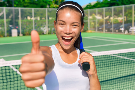 Happy Asian tennis player girl showing thumbs up hand sign after game fun holding racket on outdoor blue hard court for summer class. Sports ethnic young woman smiling of satisfaction. Stock Photo
