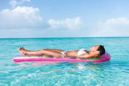 Luxury summer vacation beach woman relaxing lying down on inflatable pool float floating on turquoise ocean sun tanning. Bikini model sleeping on holiday.