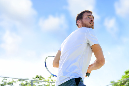 Tennis player man playing game hitting ball finishing serve outdoor. Sport fitness athlete outside with tennis racket. Fit young male caucasian professional living healthy active lifestyle. Stock Photo