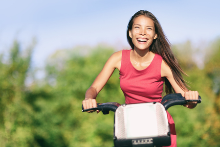 City biking Asian girl riding bike in town on summer day laughing in green background. Happy multiracial woman outdoors. Urban lifestyle
