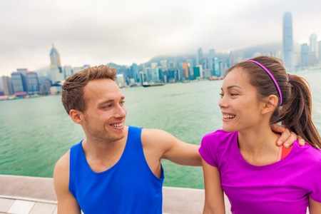 Happy couple runners living a fit active healthy lifestyle in Hong Kong city laughing together after run workout outdoors. Interracial people happy wearing sportswear on sightseeing tourism travel. Stock Photo