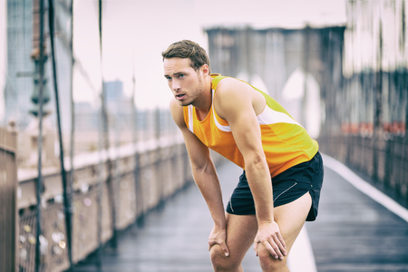 Tired runner taking a break breathing during jogging workout training on Brooklyn bridge in New York City, NYC active healthy lifestyle. Man running outdoors. Stock Photo