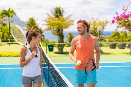 Tennis players friends having fun laughing playing on outdoor court. Couple or mixed double tennis partners outside in summer. Happy young people, woman and man living healthy active sport lifestyle. Banque d'images