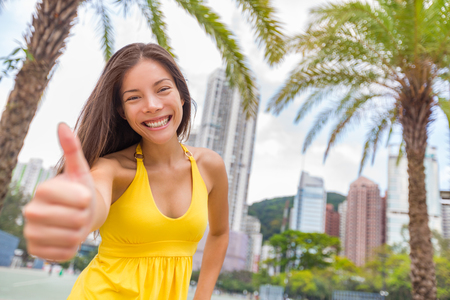 Happy chinese girl doing thumbs up in satisfaction in Hong Kong city, Asia China travel lifestyle. Young smiling multiracial woman.