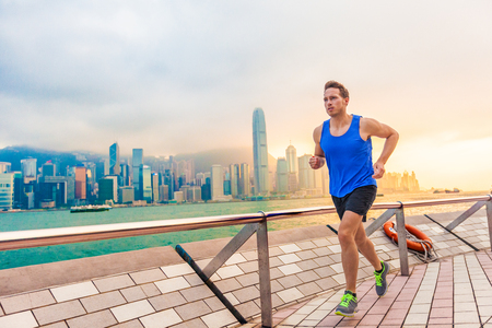 Running man runner in Hong Kong city urban skyline. Caucasian athlete training cardio jogging on the promenade of Victoria Harbor in HongKong, China, in afternoon sunset during summer. Stock Photo