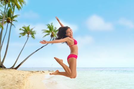 Beach fun summer vacation under the sun joyful happy bikini woman jumping of joy on Tahiti luxury travel destination. Asian girl happiness jump. Stock Photo