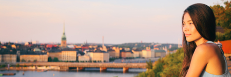 Europe travel Sweden tourist Asian woman looking at Stockholm old town landscape banner watching sunset from Monteliusvagen overlooking Gamla Stan, the old town. Sweden. Scandinavian summer vacation.